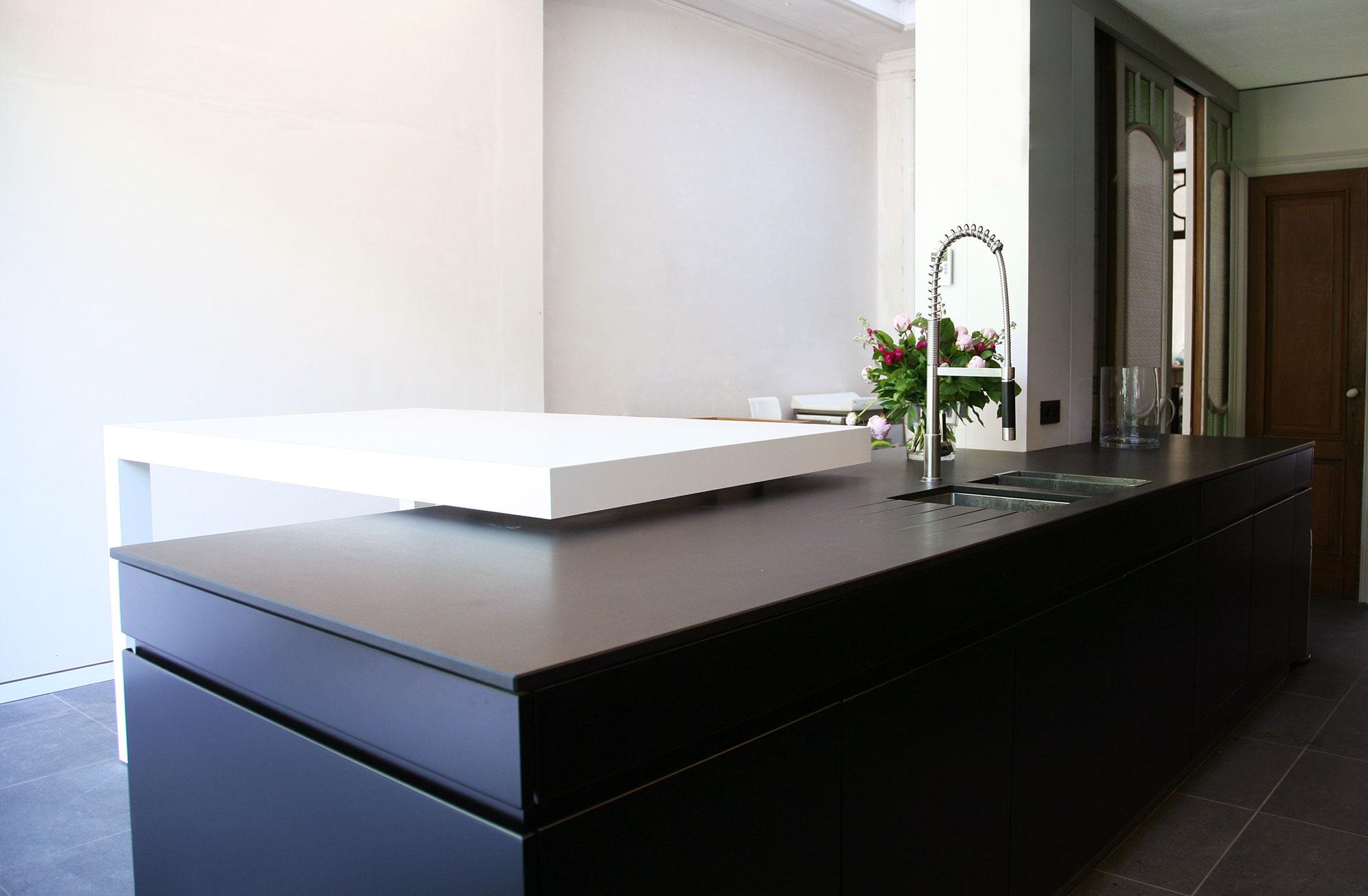 Het kookeiland werd op maat ontworpen door de interieurarchitect van AAA. Het witte tafelblad zweeft boven het zwarte kookvlak en creëert dynamiek in de ruimte.