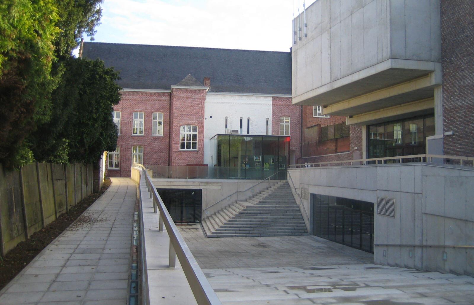 Overzicht van de betonnen buitenaanleg en het verlaagde binnenplein. Door de vorm van de trappen kan deze ruimte gebruikt worden als buitenpodium.