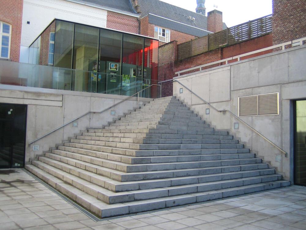 De betonnen trap zorgt ervoor dat het verlaagde binnenplein bereikbaar wordt. Daarnaast functioneert deze ook als tribune, wanneer er opvoeringen buiten gebeuren.