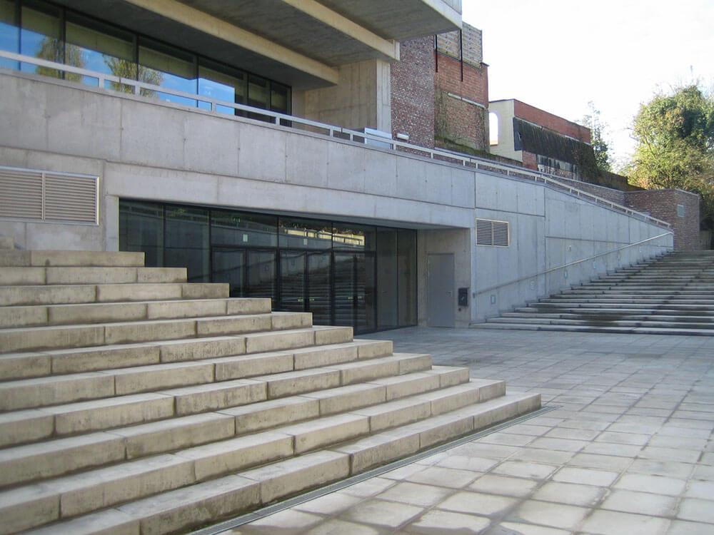 De ingang bevind zich naast de betonnen trappen.