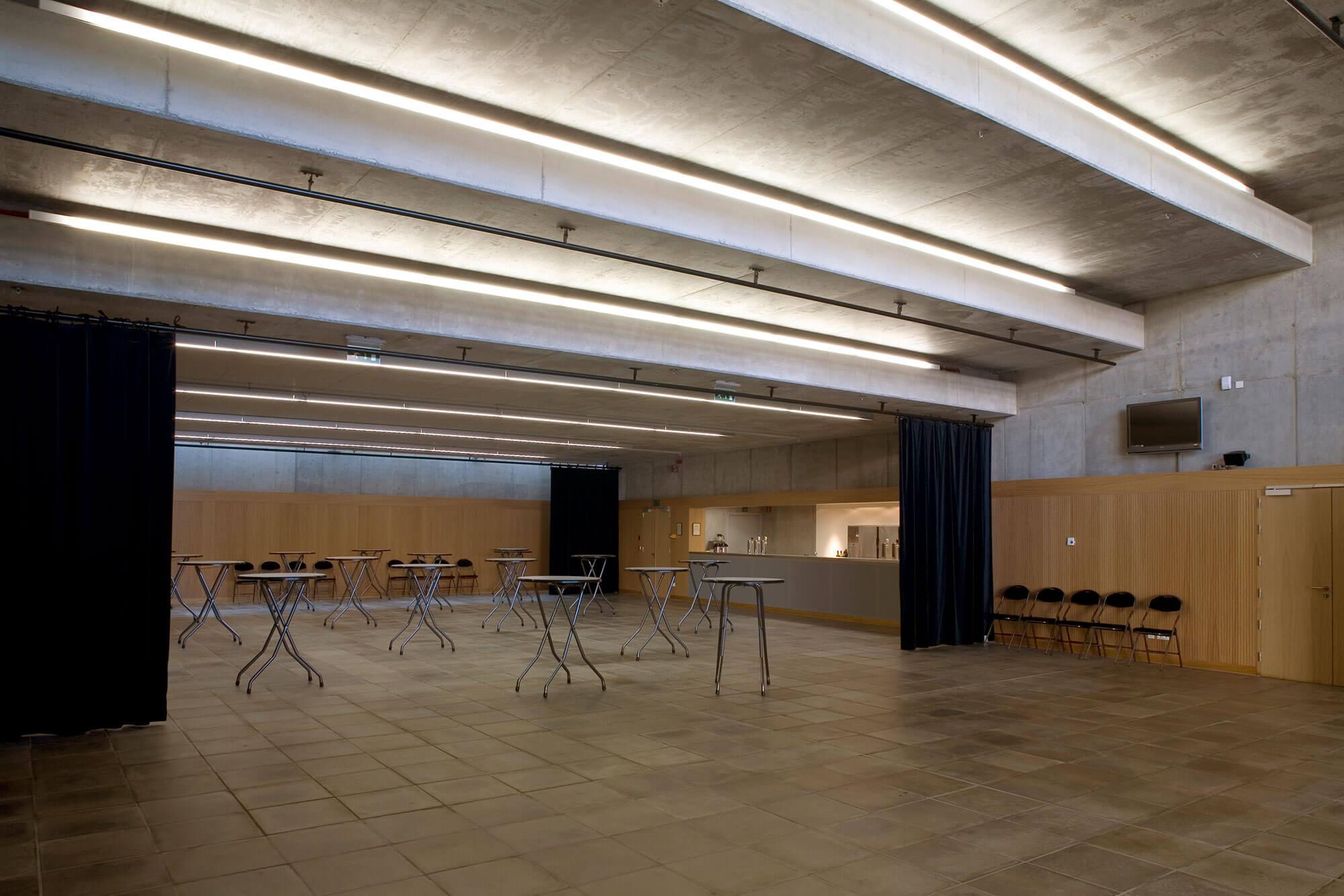 De foyer/receptieruimte werd voorzien van indirecte lichtlijnen, een grote bar en de mogelijkheid om de zaal in aparte zones te verdelen door middel van zware doeken.
