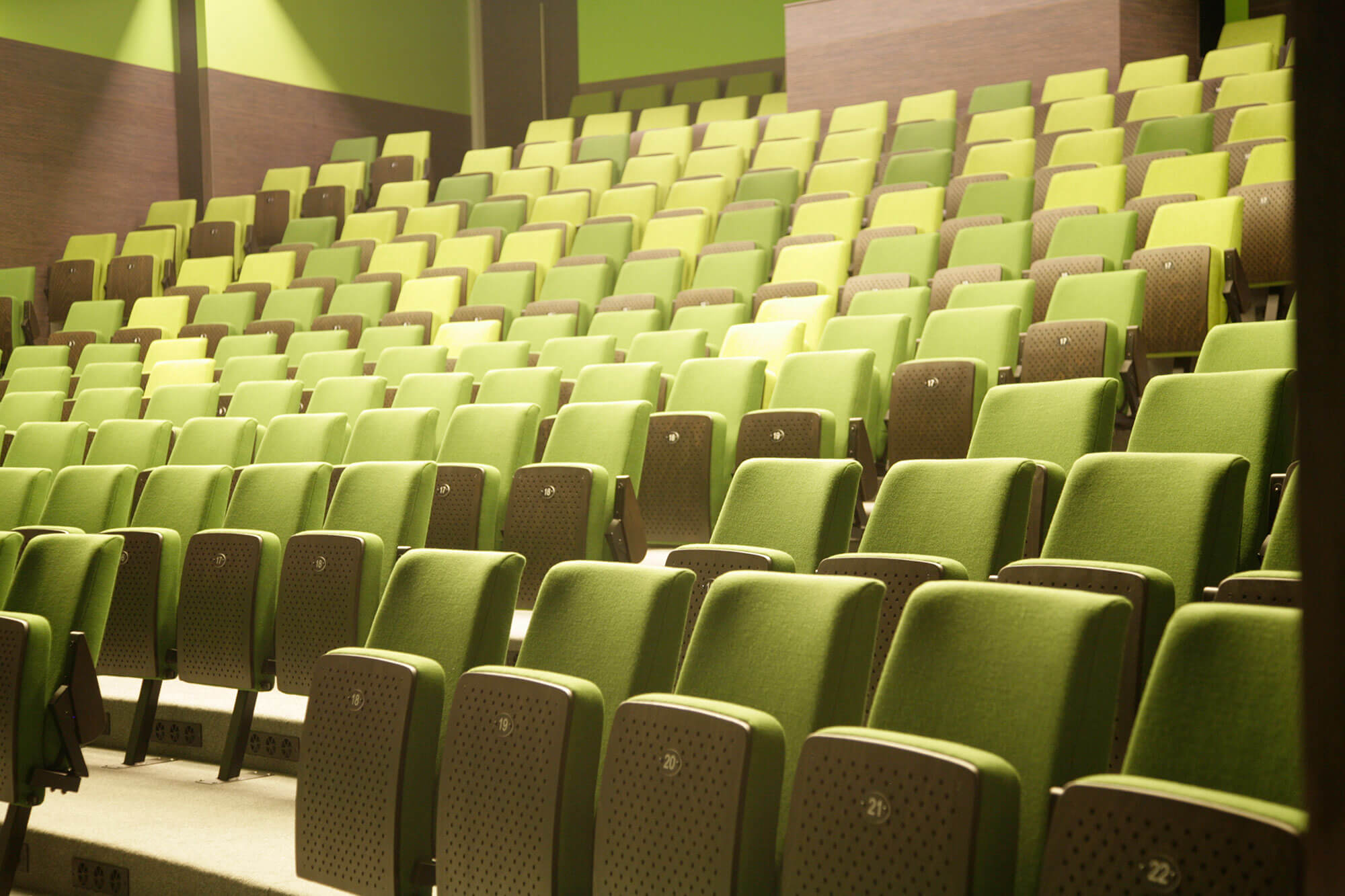 Door schakeringen in de groene kleur van de zetels wordt er een dynamisch beeld in de zaal gecreëerd.