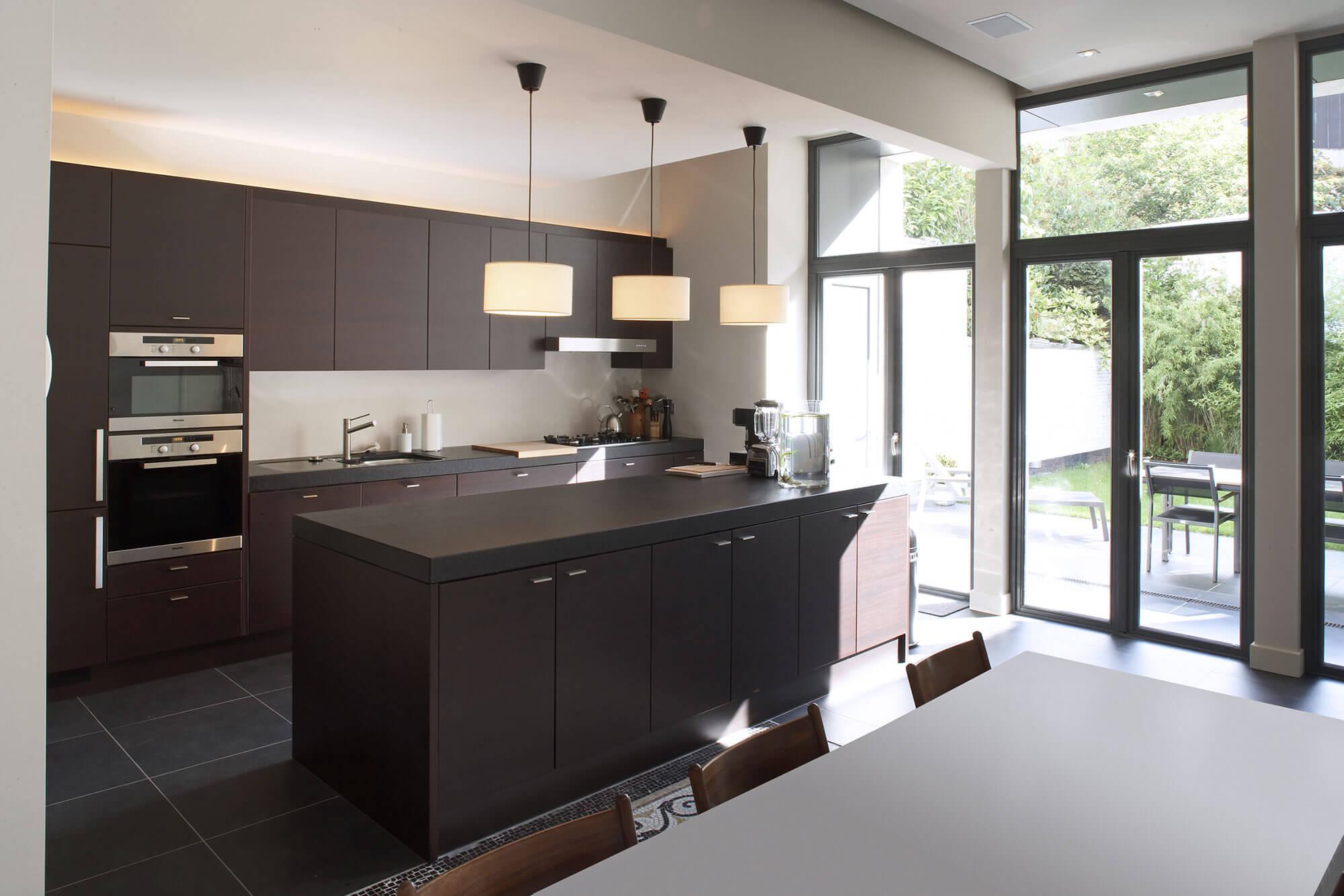 De volledig gerenoveerde keuken werd voorzien van donkere ingebouwde kasten, een ruim kookoppervlak en grote ramen voor een natuurlijk belichte leefomgeving.
