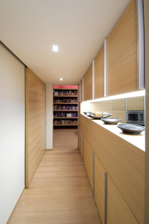 De gang loopt langs de keuken en is voorzien van inbouwkasten.
