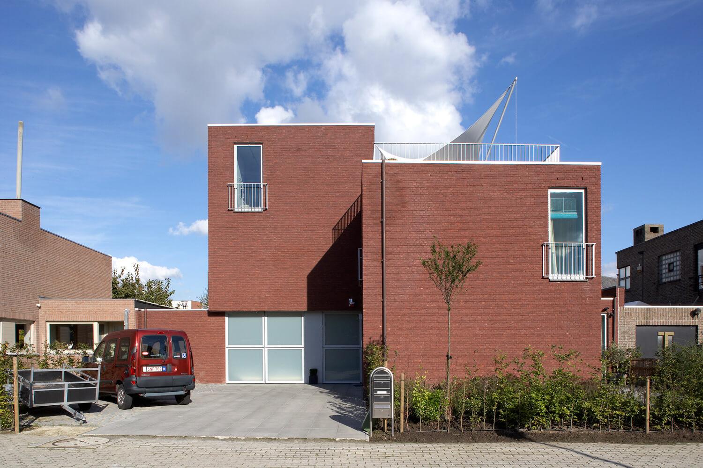 De voorgevel van de drie-in-één-woning werd sober gehouden. Er werden ook ruime parkeerplekken voorzien voor de bewoners.