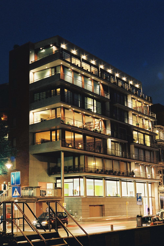Nachtbeeld van het verlichte appartementsgebouw.