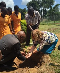Amber planting a tree for the future growth at the school
