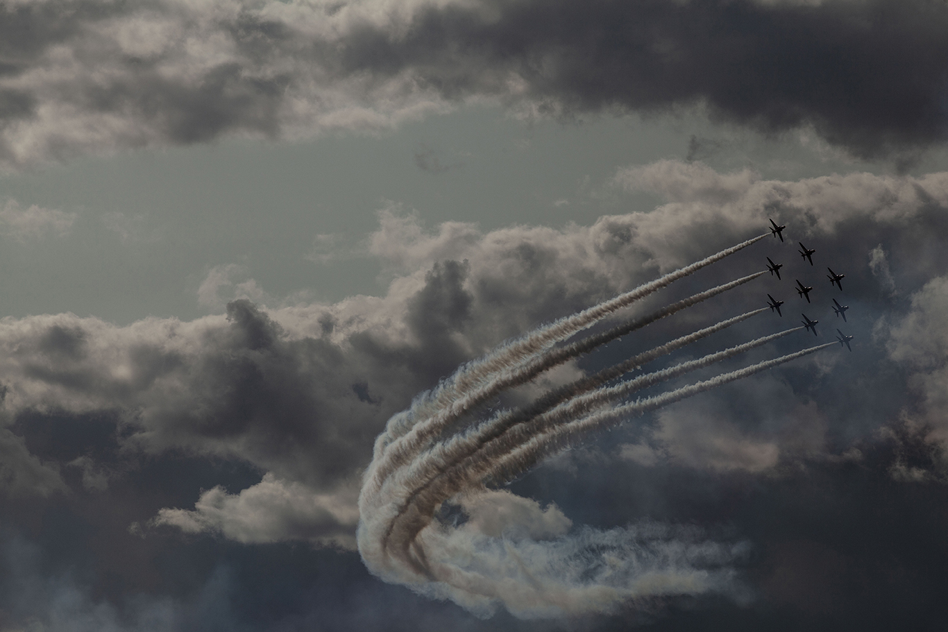 RAF Red Arrows perform against the fluffy clouds. Dunsfold, Surrey
