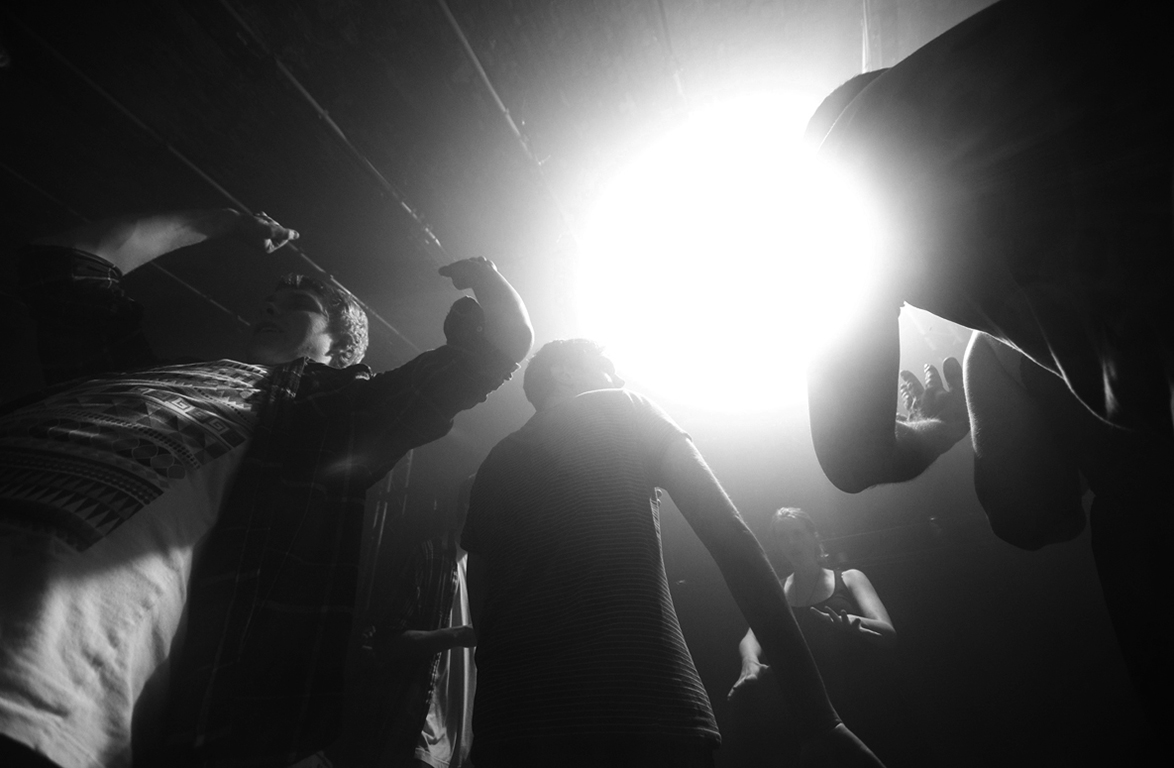 Party goers dance with hands aloft. Warehouse Project, Manchester