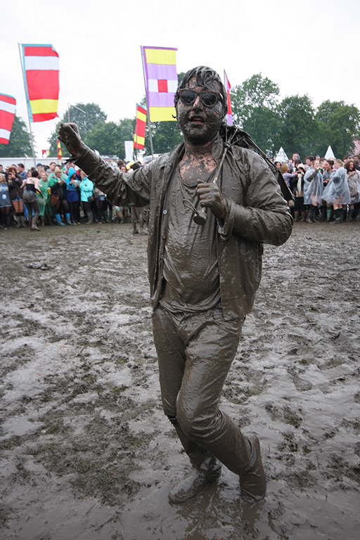 A Mudded lover poses for me whilst there is a pause in the music for the local Plattfields Church early evening service. Music was stopped for 45 minutes. Parklife Festival. Manchester