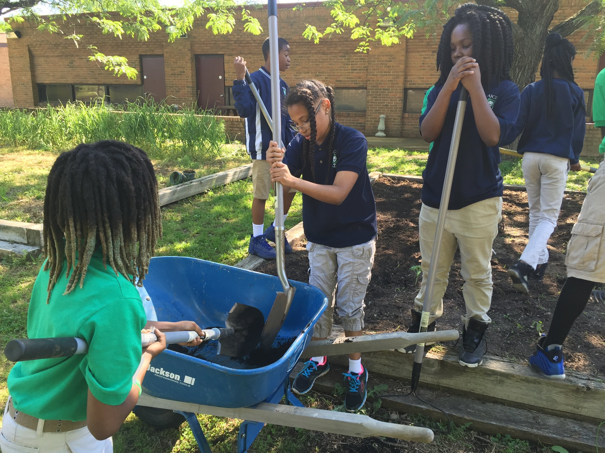 Elementary students at AJCES preparing raised beds for Spring planting, 2017