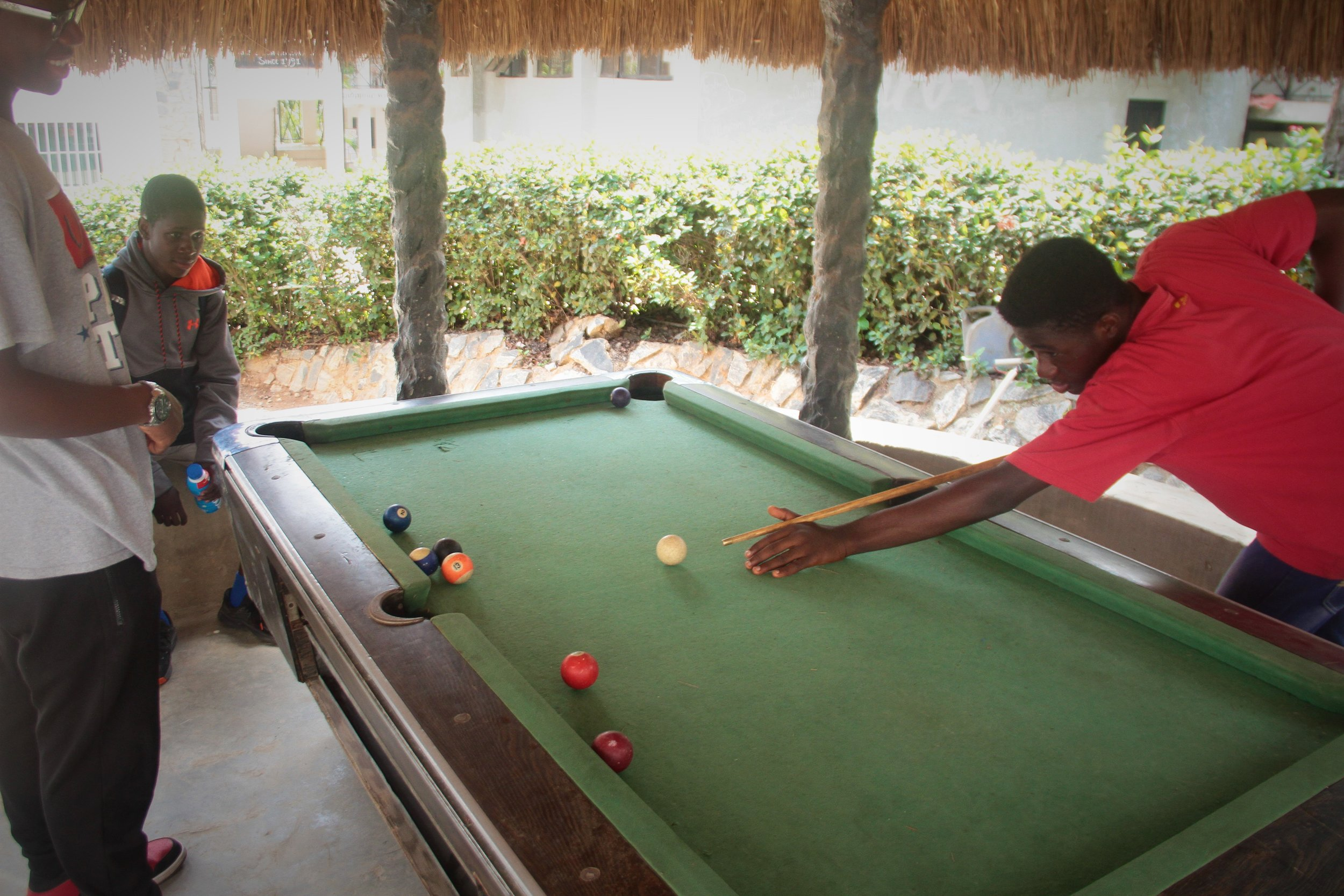 12th graders enjoying a game of pool during their break.