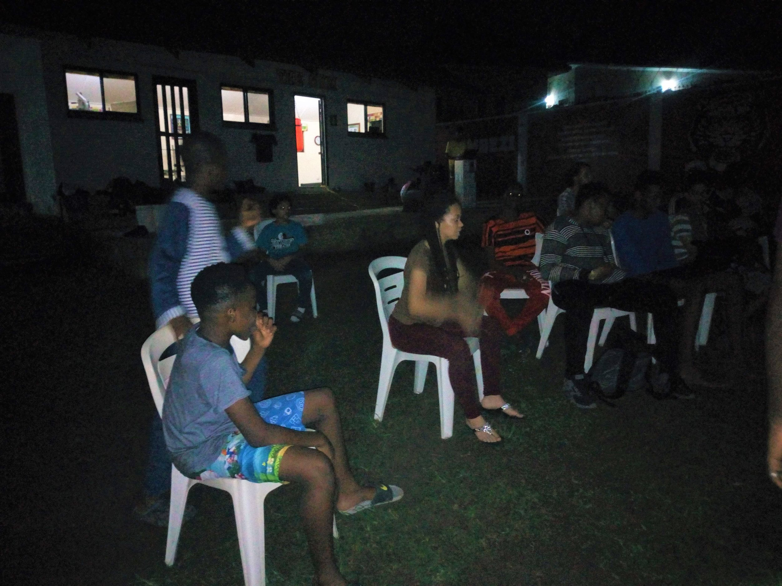 """After the Scavenger Hunt and Water Balloon Fight, students played """"Guess the Song"""" while sitting near the bonfire and eating roasted marshmallows!"""