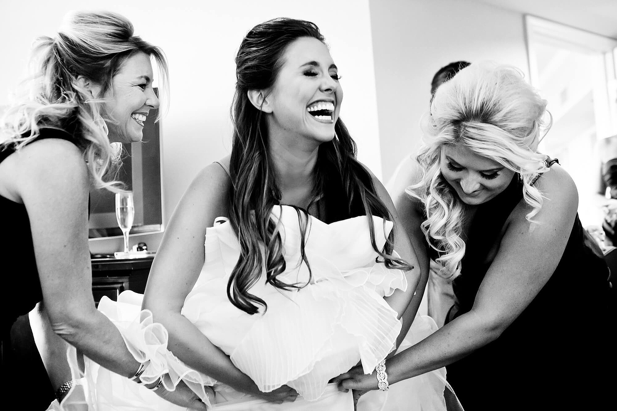 25-chase-park-plaza-bride-laughing-putting-on-dress.jpg