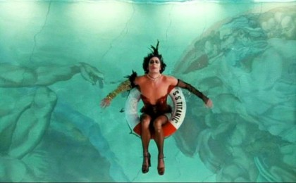 Frank-N-Furter lays in a pool with Michelangelo's 'The Creation of Adam'