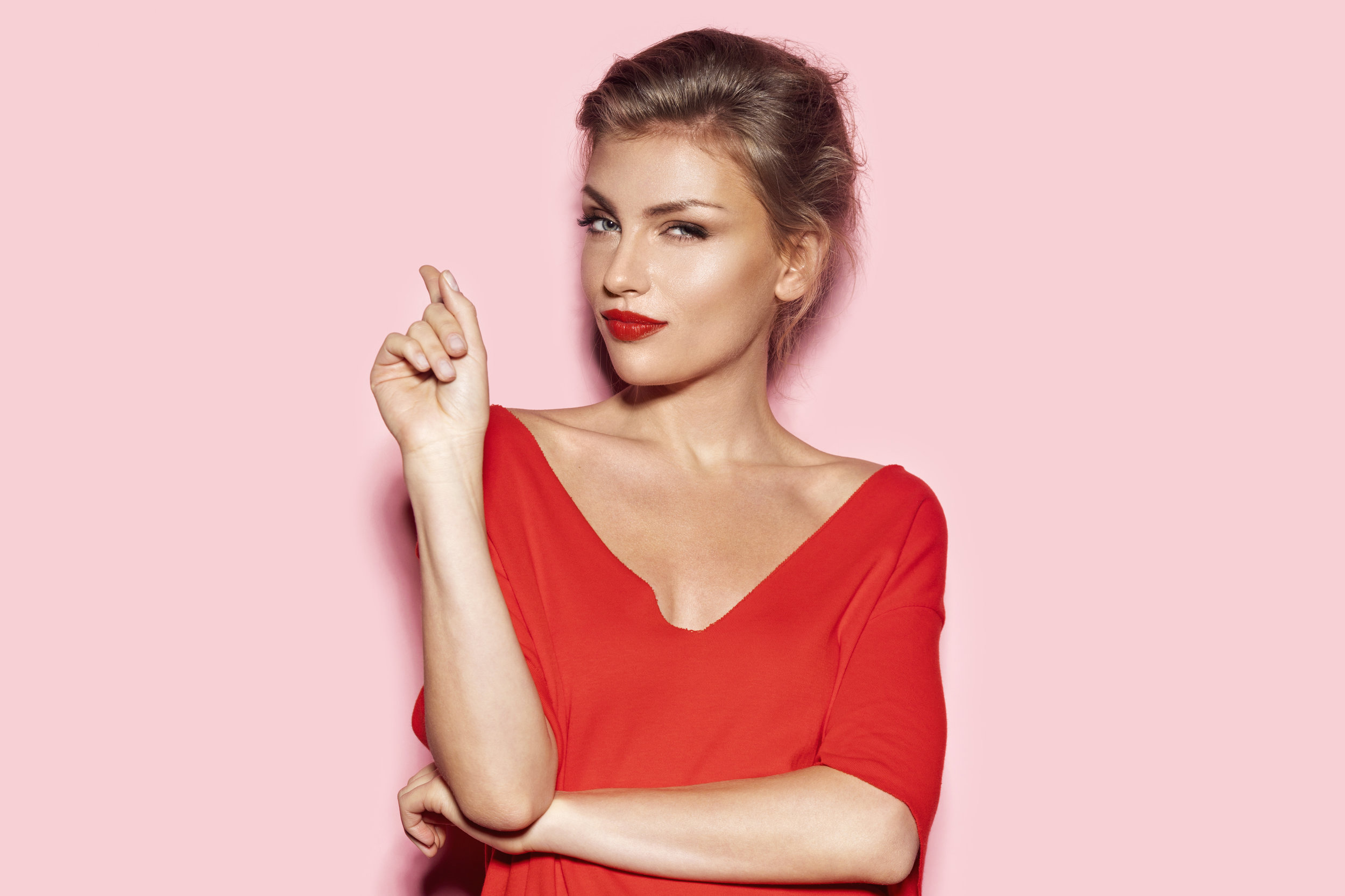Blonde headed woman with beautiful acne free complexion in red top wearing red lipstick giving the side-eye and casually pointing in a gesture indicating she has this under control.