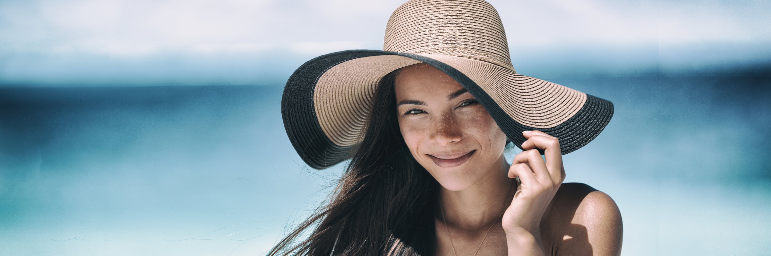 Woman with long dark brown hair flowing in the breeze and skin that is free of sun damage smiling and wearing sun hat with blue ocean background.