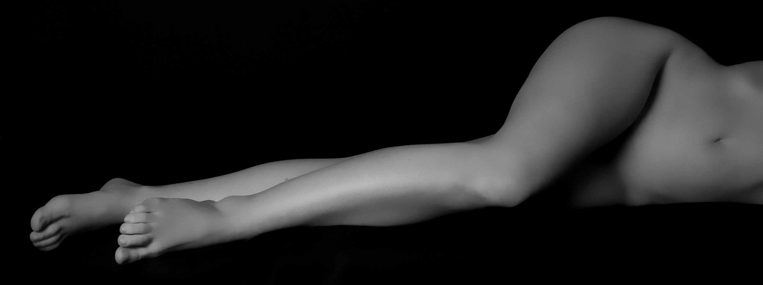 Black and white photo of woman's body from naval down. She is lying on her side and her skin is smooth and hairless after her IPL laser hair removal treatments.