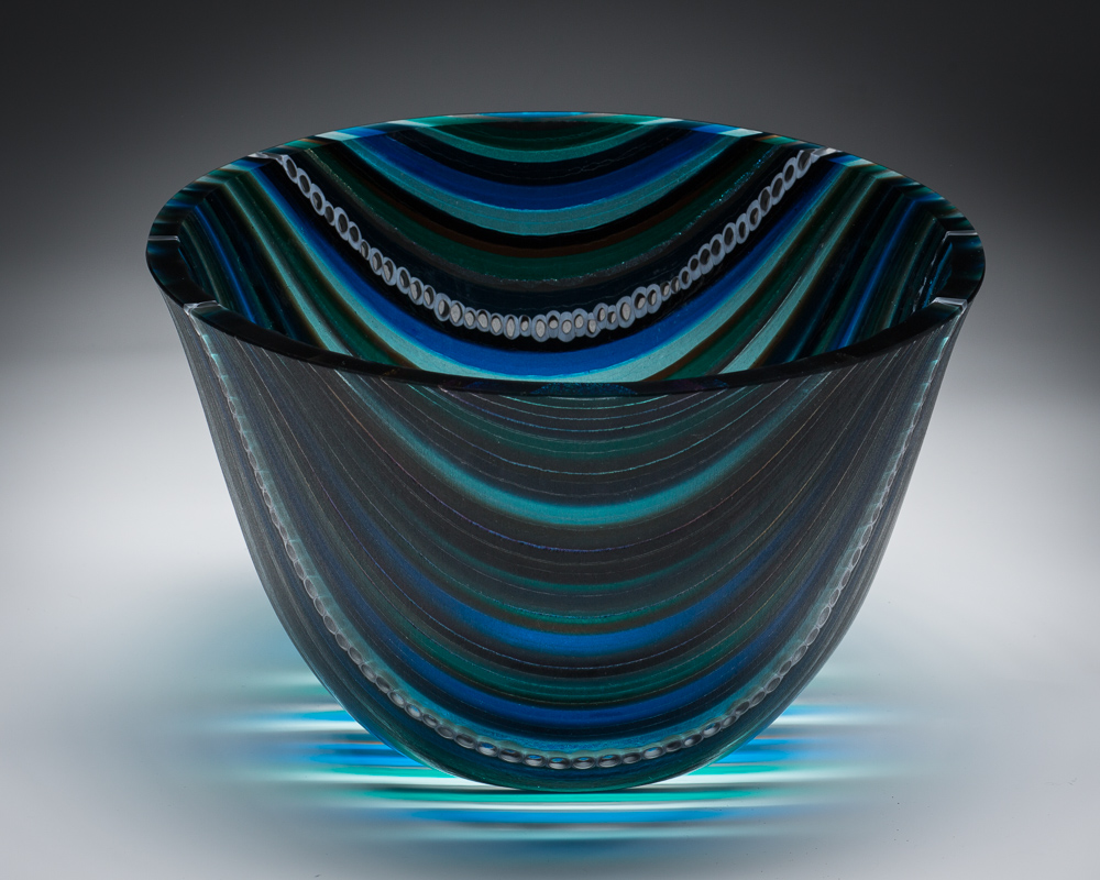 """Blue Lagoon""    7""H X 9.5"" W   This vessel began with many 1/4"" strips of glass placed on edge and fused together to form one flat piece. A 16"" circle was then cut.  The ""slumping"" process is where the glass is placed on a mold and warmed in the kiln until the glass takes the shape of the mold. To gain this shape is a 3 step processes using graduated sized molds to attain the shape.  The edge is ground and polished using a grinding wheel and water."