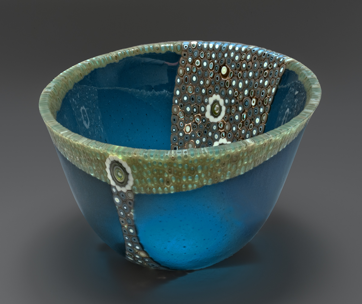 "This vessel began by cutting a 14"" circle and offsetting it to allow the addition of pre-made murrine to be added along the rim and throughout the center. It was then fired to make one flat 16"" circle  The ""slumping"" process is where the glass is placed on a mold and warmed in the kiln until the glass takes the shape of the mold. To gain this shape is a 3 step processes using graduated sized molds to attain the shape.  The edge is ground and polished using a grinding wheel and water"