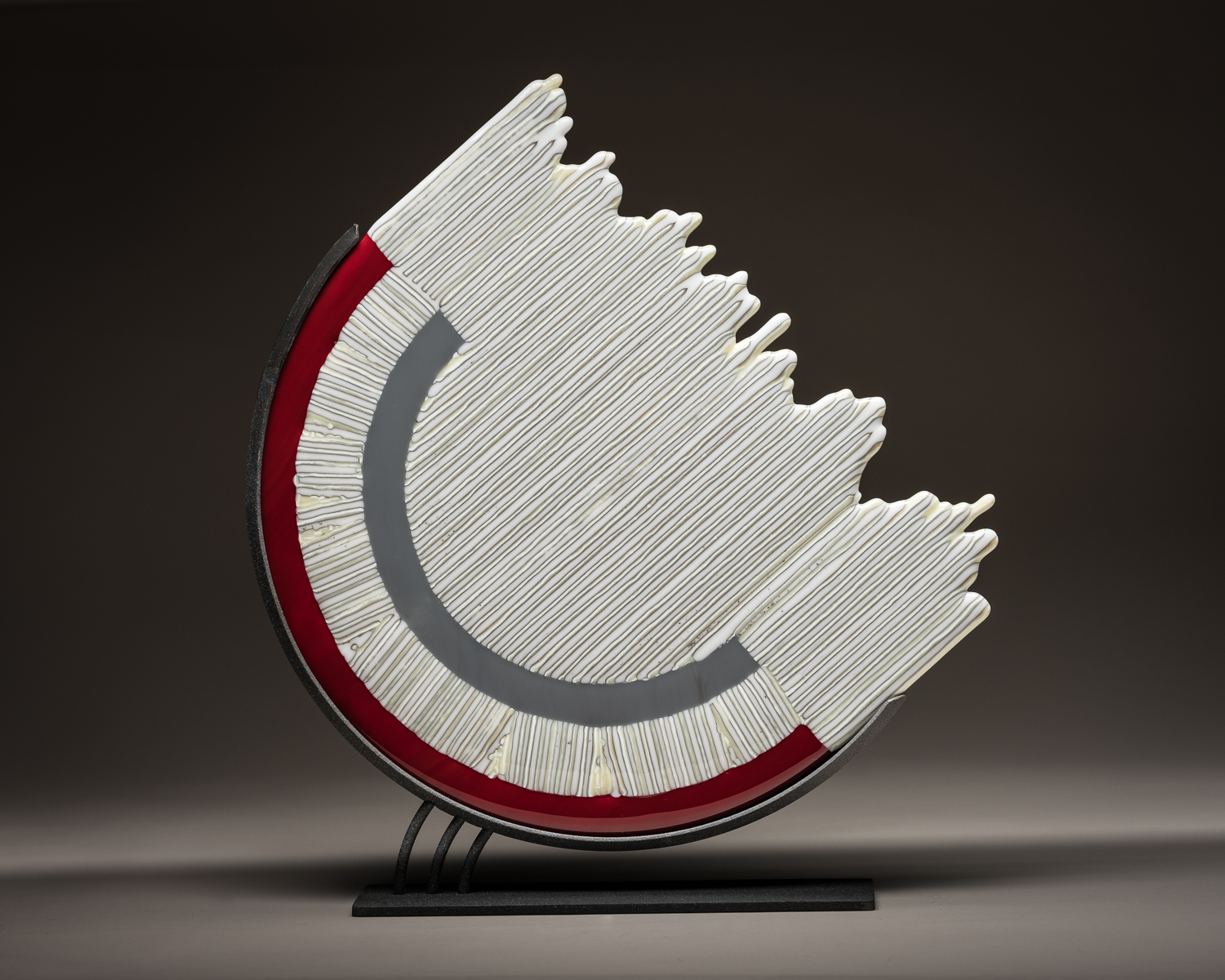 """Magnetic Motion""    14"" sculpture in stand   This piece began as 2 round rings, one red and one gray. They were then cut on angle. Different lengths of 1/4"" strips of two other colors were placed on in and fired in a kiln."