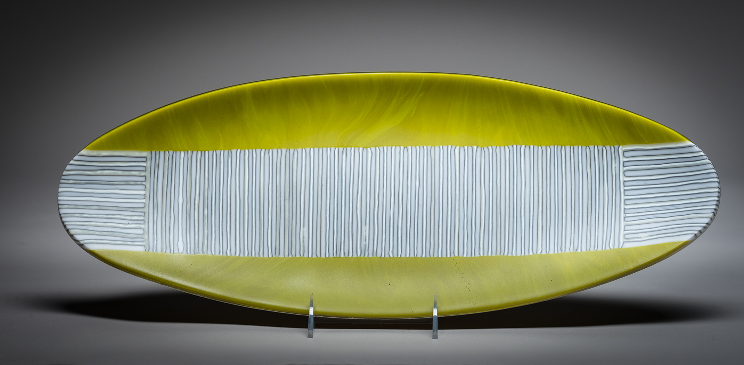 """""""Quiet Moment""""    19"""" functional platter   This piece was created using green glass and 1/4"""" strips of two other colors of glass placed on end and fused together to make one oval platter. The piece was sandblasted and slumped giving it's shape."""