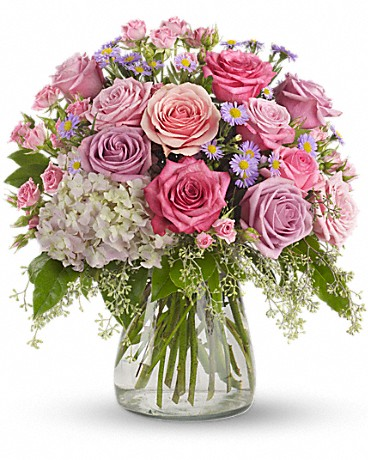 Your Light Shines    This softly elegant gesture of condolence and affection honoring the memory of a life well lived is a gentle touch during a difficult time. Lavender and pink flowers such as roses, hydrangea, monte cassino asters, eucalyptus and salal are arranged in a clear glass hurricane vase.    Buy Now>>