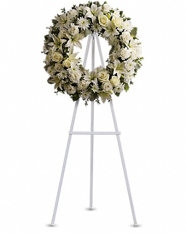 Serenity Wreath    Bright white blossoms will create a serene display at any funeral or wake. A standing wreath created from fresh white flowers such as roses, Asiatic lilies, carnations and cushion spray chrysanthemums - accented with greenery - is delivered on an easel.    Shop Now>>