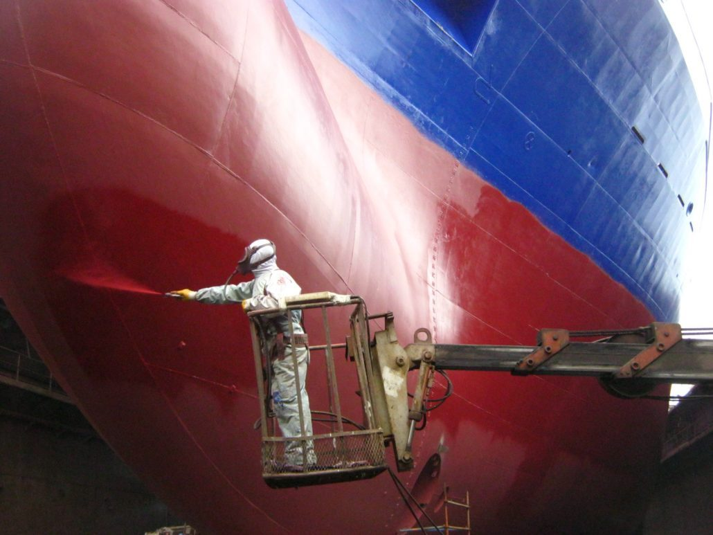 Protecting boat hulls with antifouling paints can lead to lower expenses in fuel. Notice, though, how guarded the painter is in this picture; the toxicity of these paints is nothing to underestimate. Photo credit: coatingpaint.com