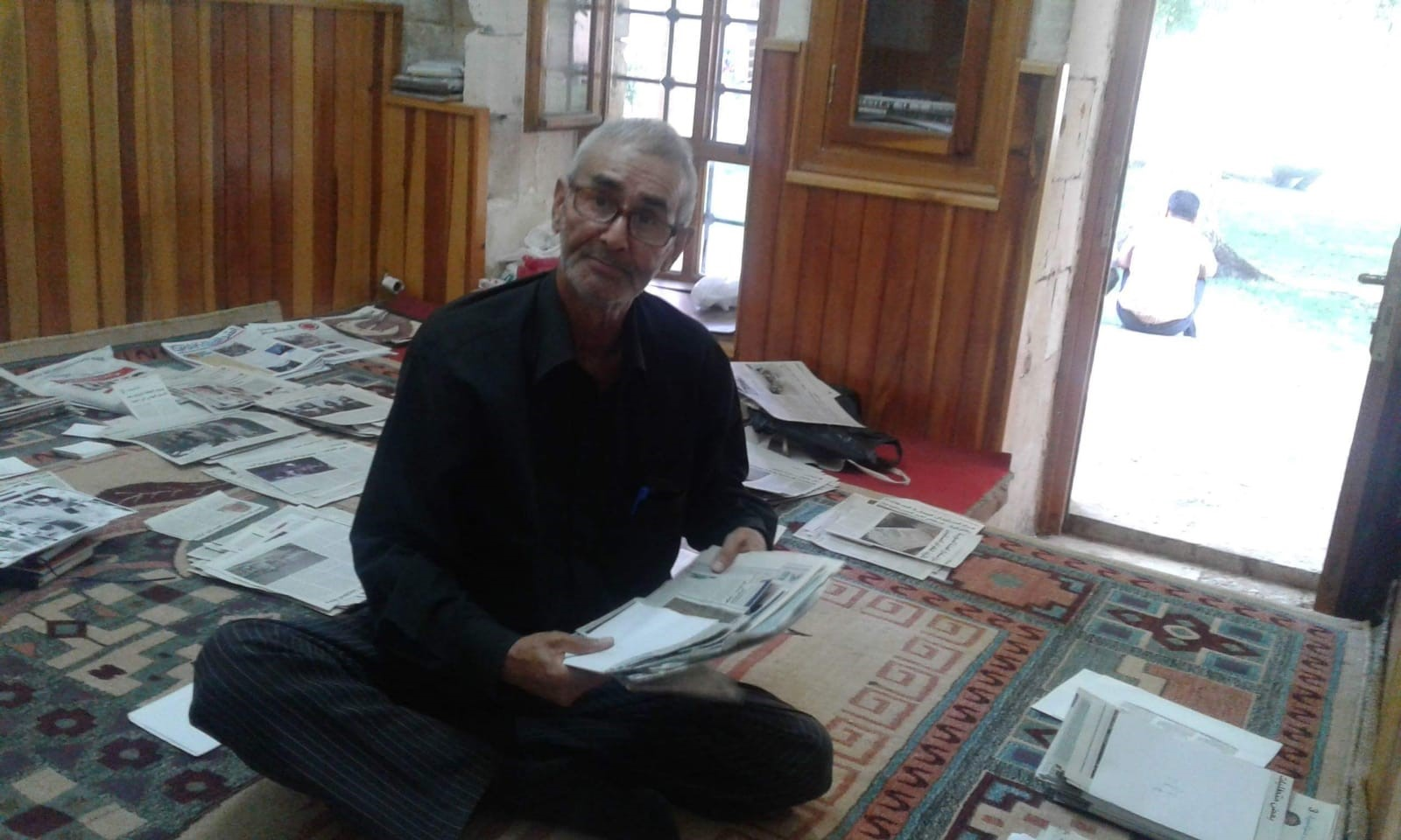 Mr. Al Taha collects newspaper articles for writing biographies in one of his house room.