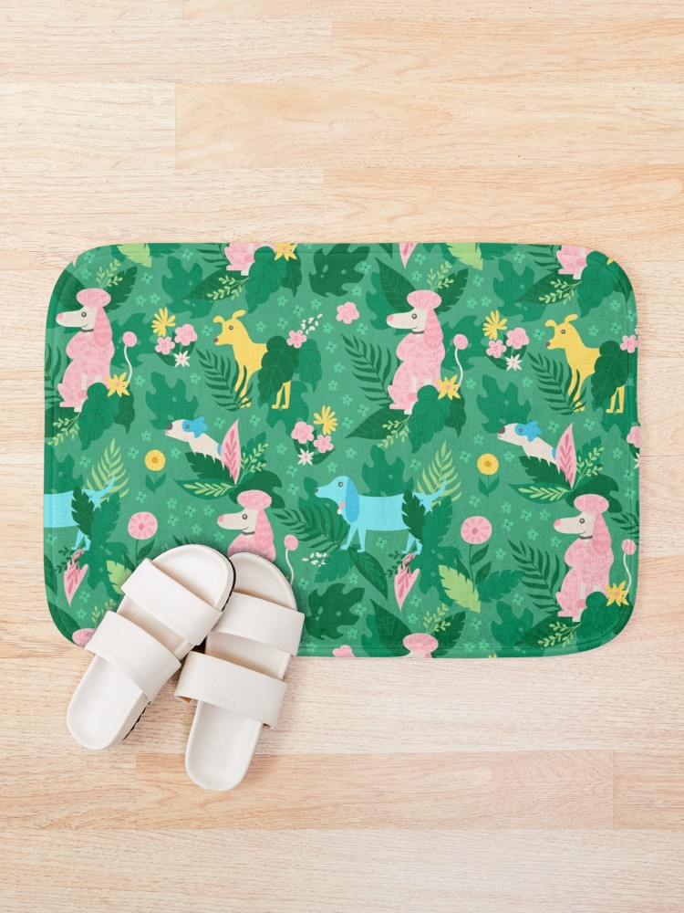 Bathmat of whimsical doggos in green, pink, and blue, with lots of flowers and leaves