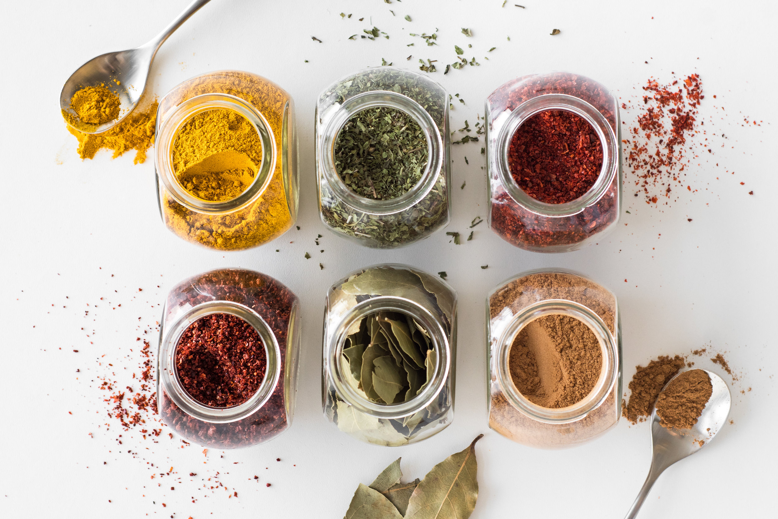 Middle Eastern spices. Clockwise from top left: tumeric, dried mint, hot ground pepper, cinnamon, bay leaves, sweet ground pepper