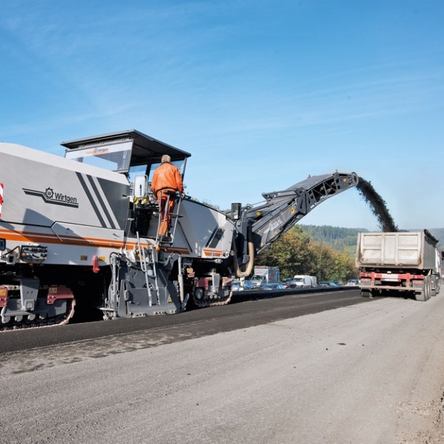 Milling Machine - A self-propelled unit having a cutting head equipped with carbide- tipped tools for the pulverization and removal of layers of asphalt materials from pavements.