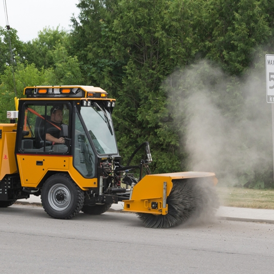 Power Sweeper - A power operated rotary broom used to clean loose material from the pavement surface.
