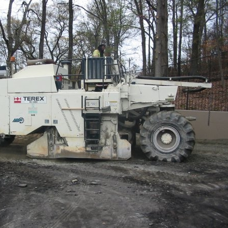 Reclaiming Machine - A self-propelled unit having a transverse cutting and mixing head inside of a closed chamber for the pulverization and mixing of existing pavement materials with asphalt emulsion. Asphalt emulsion (and mixing water) may be added directly through the machine by a liquid additive system and spray bar.