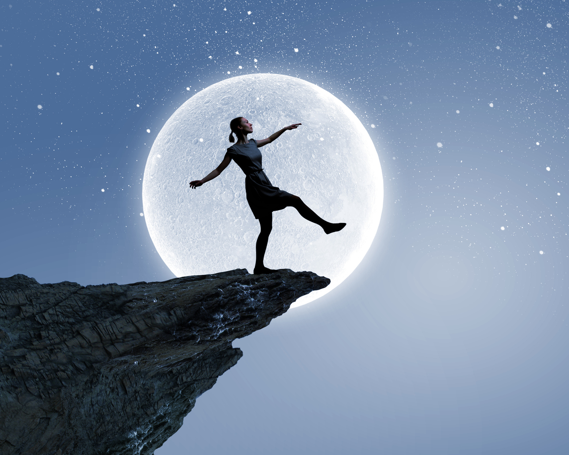 Woman sleepwalking on the edge of a cliff