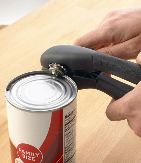 A hand using a can opener.