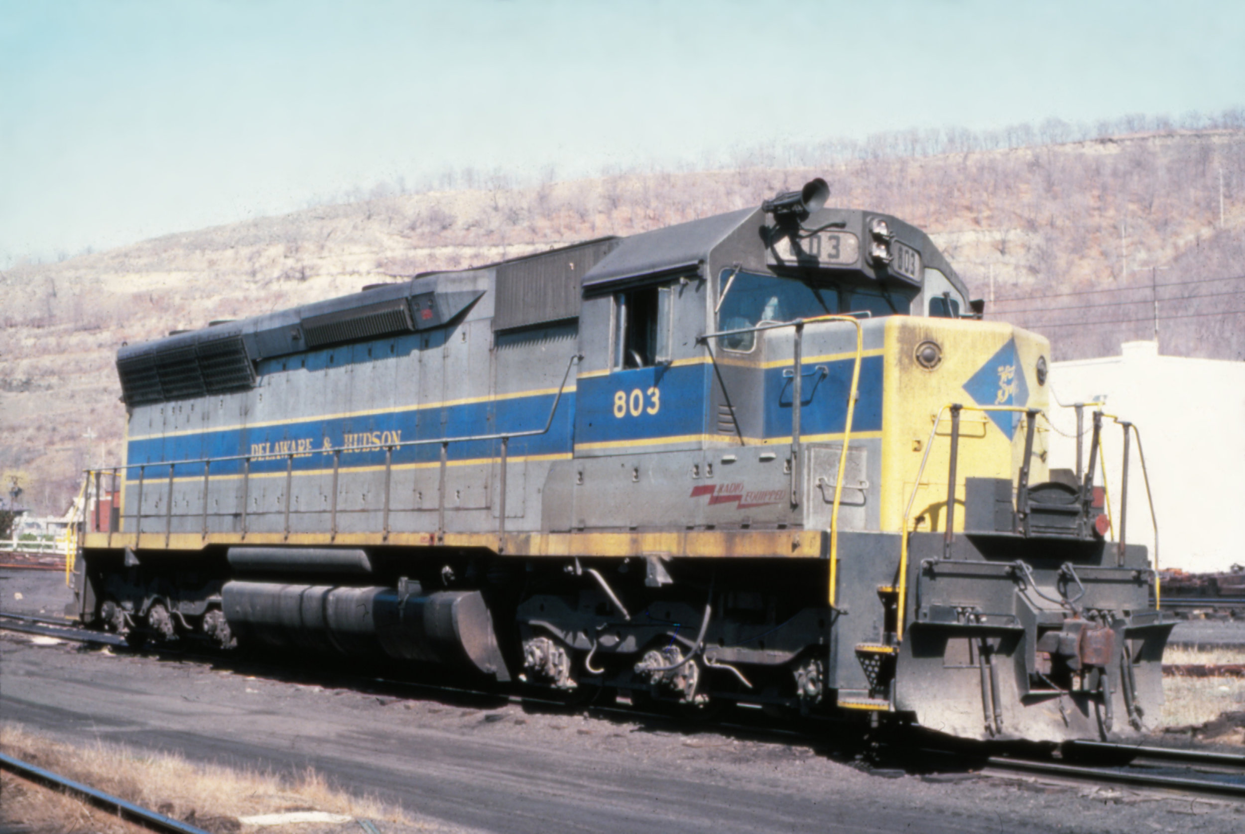 In 1977, D&H SD45 #803 shows off its L-shaped windshield and patched EL paint scheme.  The Garbely Publishing Company collection