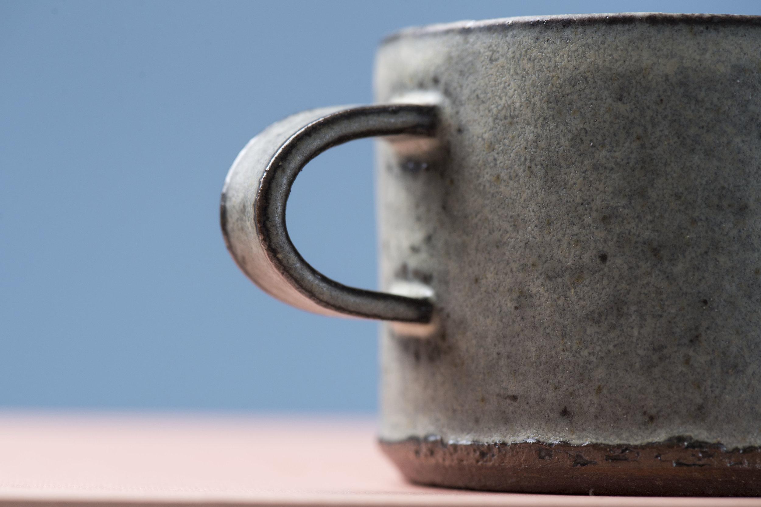 Hånddrejede kaffekopper i rød eller grå stentøjsler.