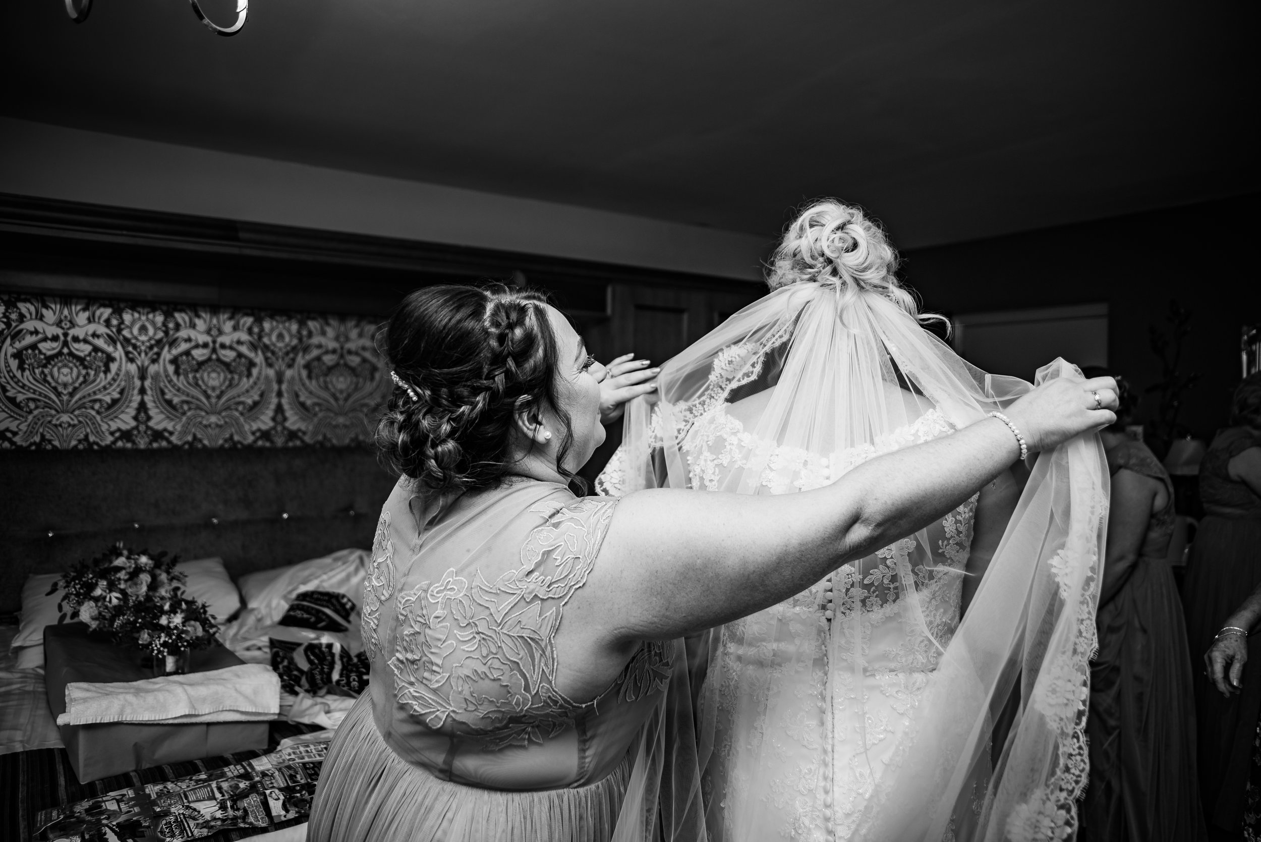 A beautiful moment the maid of honour attaches the veil. This is a perfect moment as the veil belongs to the maid of honour and she wore it for her wedding, it's the brides something borrowed. Wedding photography is about capturing all these moments because they are more than capturing memories, its about telling your story.