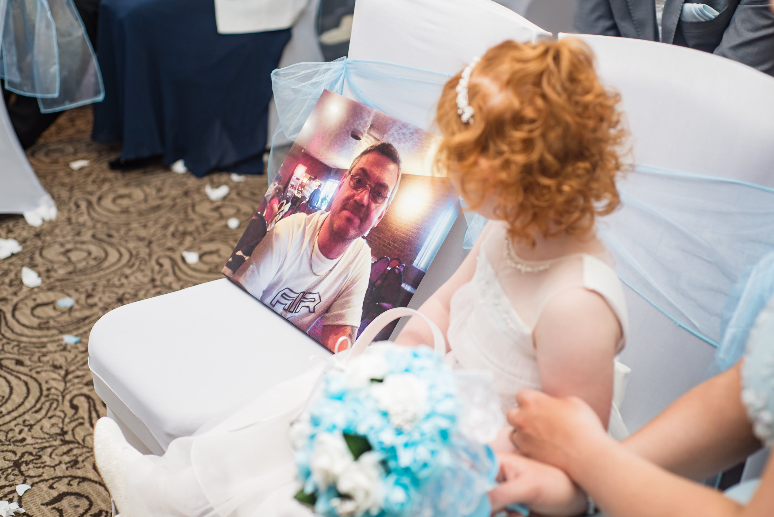 wedding photography and wedding videography, beautiful shot of the flower girl looking at her late grandfather during the ceremony
