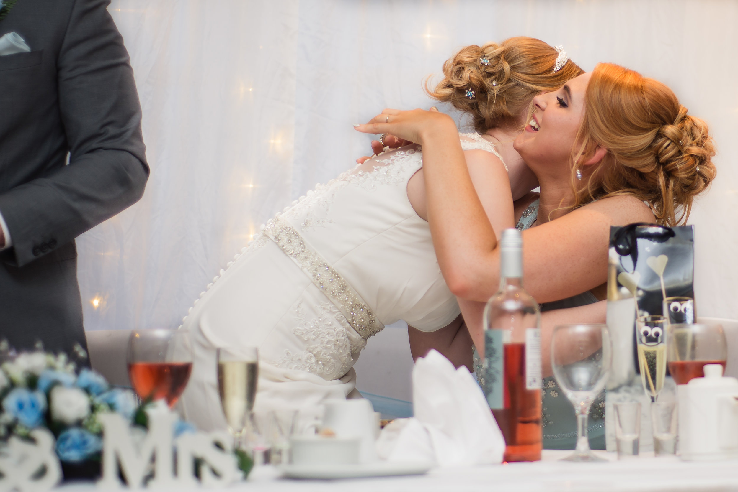wedding photography and wedding videography, emotional bride hugging her maid of honour