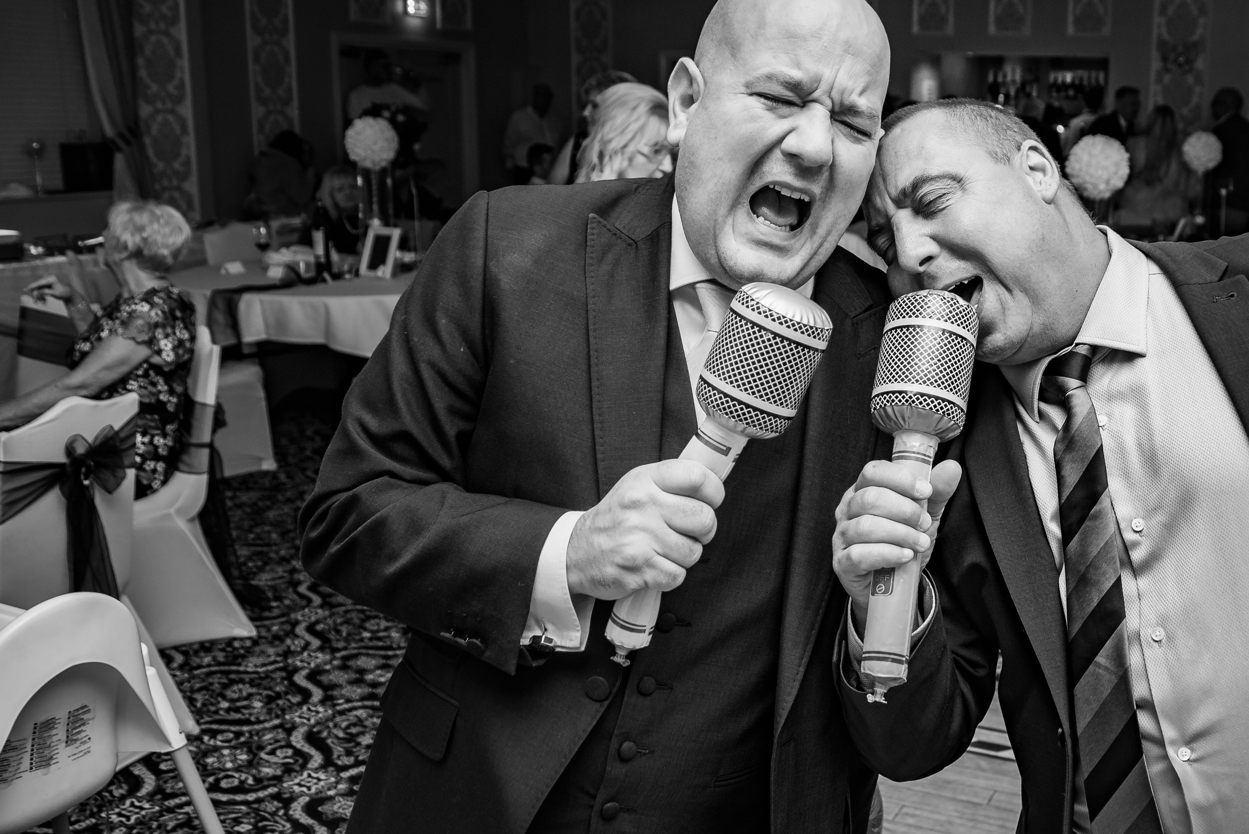 black and white wedding photography groom and guest have something to sing about
