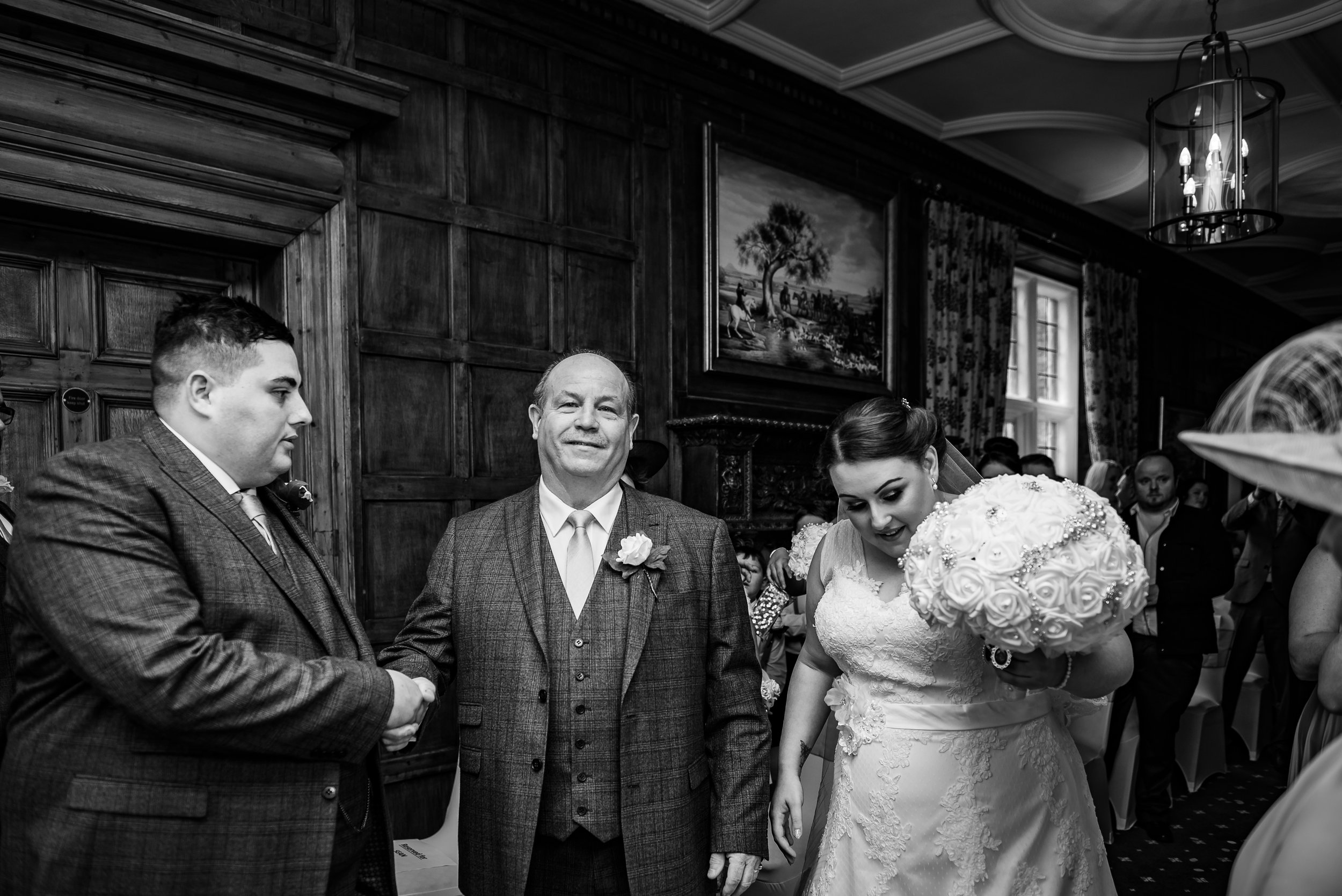 black and white wedding photography father of the bride hands her over to her future