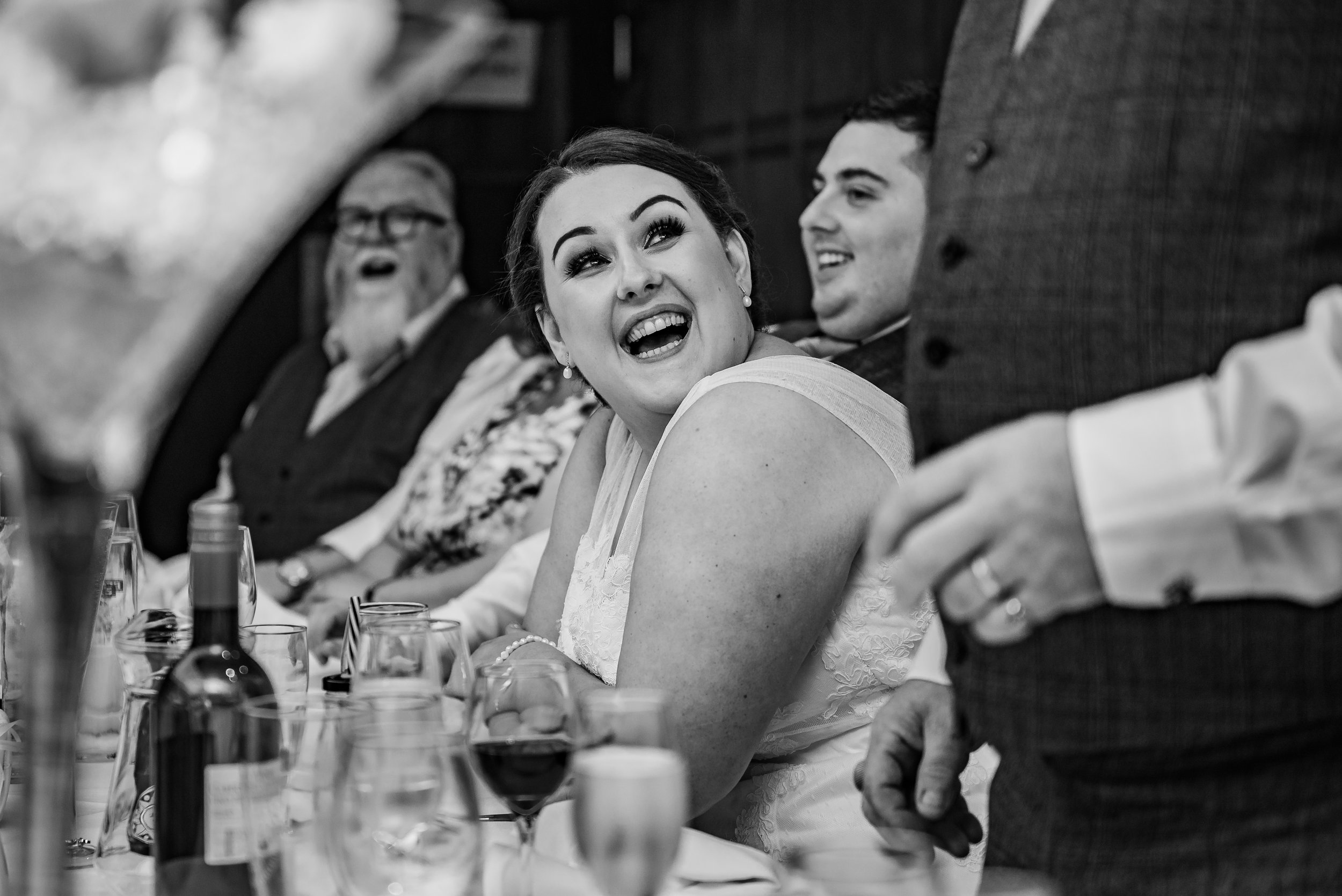 black and white wedding photography happy laughing bride during speeches