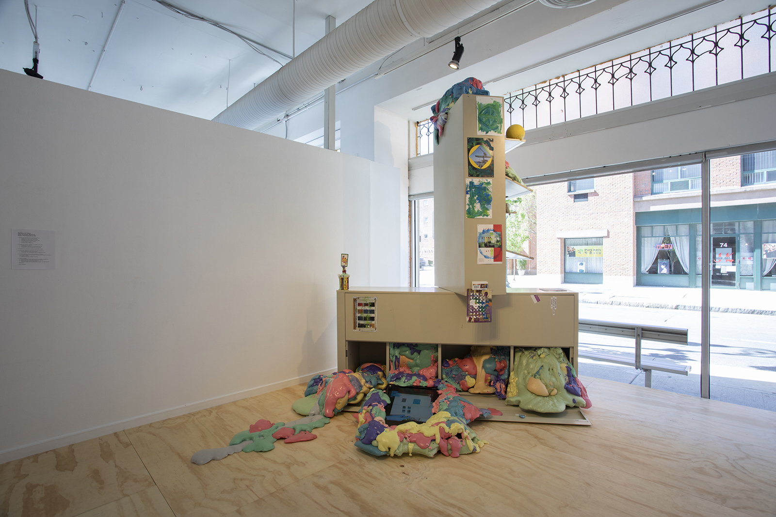"""Jeff Ostergren, Color is fundamentally involved in the making of culture from the human body (2018/2019). Metal cabinets from Bayer Corporation, polyurethane foam, pigment, oil paint, book pages, pharmaceuticals, found office supplies, magnets, flatscreen monitor, speakers, digital video TRT 12:41. (Installation View of """"Perverse Furniture"""" at Artspace, New Haven, CT (2019). Photo Credit: Jessica Smolinski.)"""