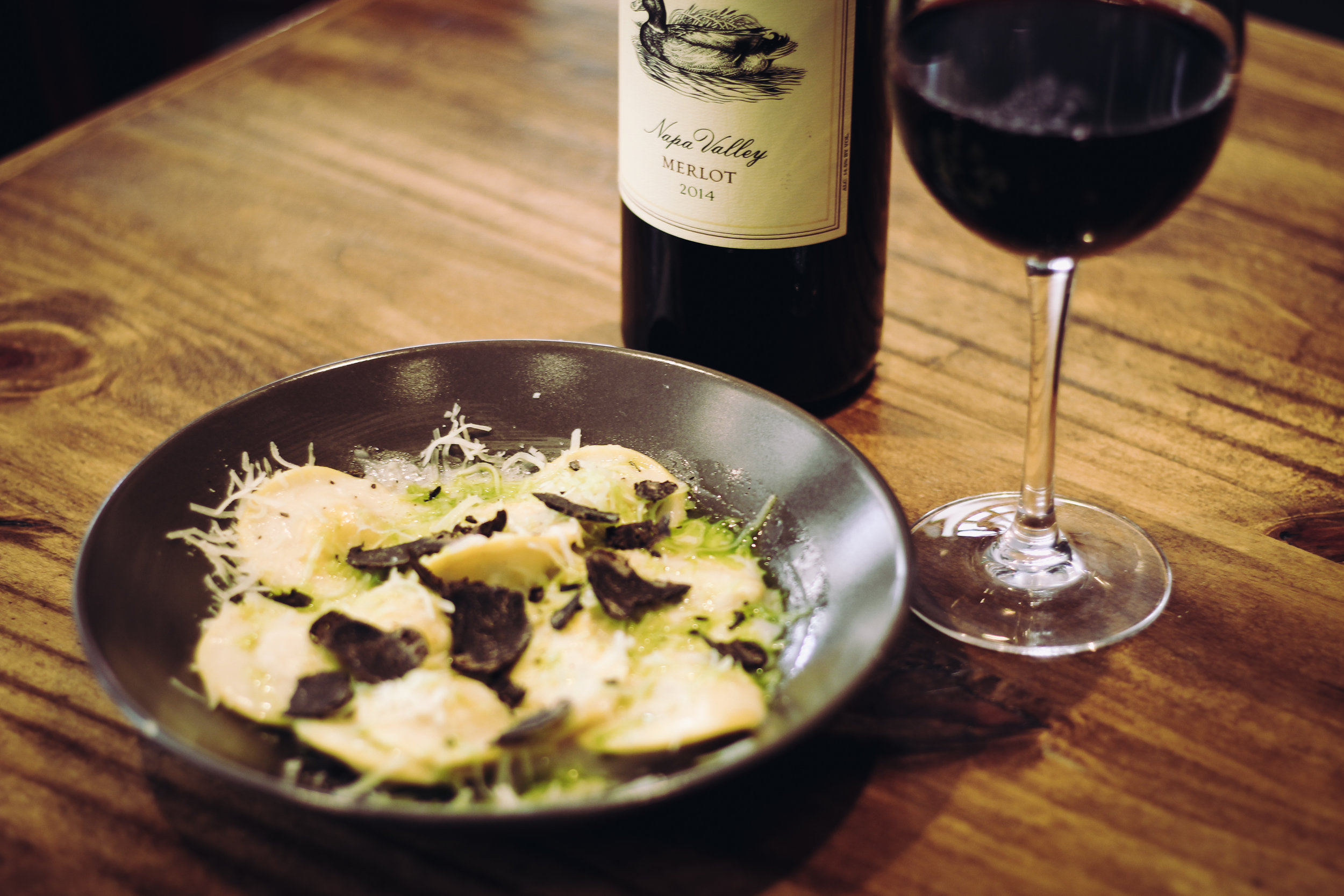 Black truffle ravioli with hand-shaved parmesan. Paired with Merlot.