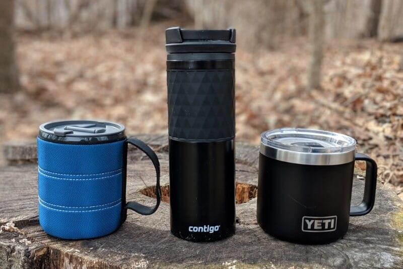 gsi infinity and contigo ceramic lined and yeti rambler 14 camping mugs sitting on stump outdoors