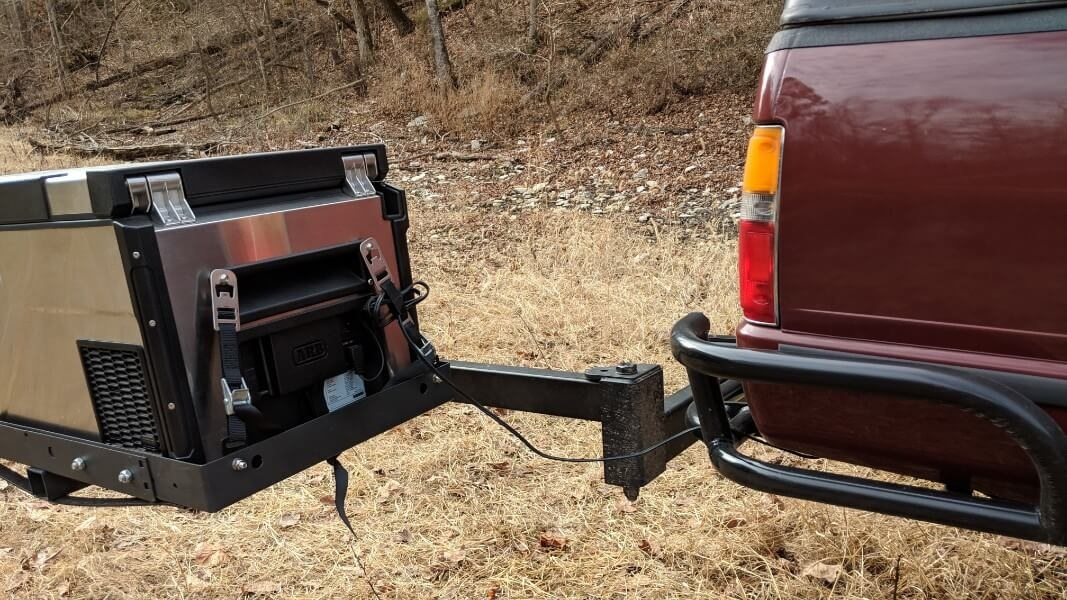 camping fridge secured to cargo carrier with tie downs on swing arm hitch mount