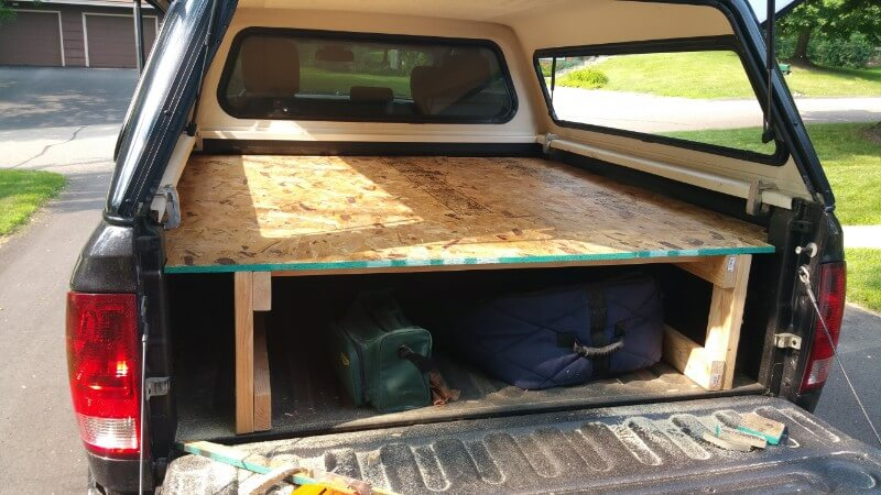 wood frame in truck bed with plywood across top as sleeping platform